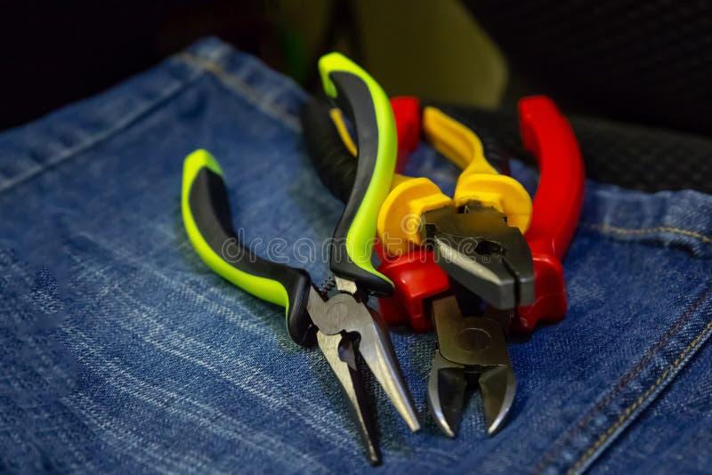 Σύνολο nippers τρία εργαλεία ενός σωρού της ηλεκτρικής ενέργειας που επισκευάζει τις κιτρινοπράσινες κόκκινες μάνδρες στο υπόβαθρ στοκ εικόνες