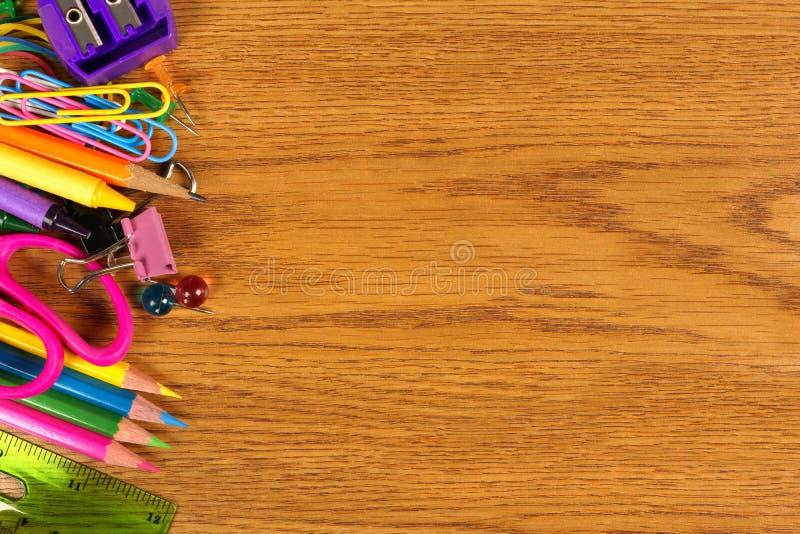 Σύνορα πλευράς σχολικών προμηθειών στο ξύλινο γραφείο στοκ φωτογραφίες με δικαίωμα ελεύθερης χρήσης