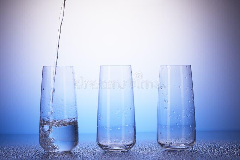 Σύνολο ενός τρίτου, δύο κενά γυαλιά κατανάλωσης Έκχυση νερού στοκ φωτογραφίες με δικαίωμα ελεύθερης χρήσης