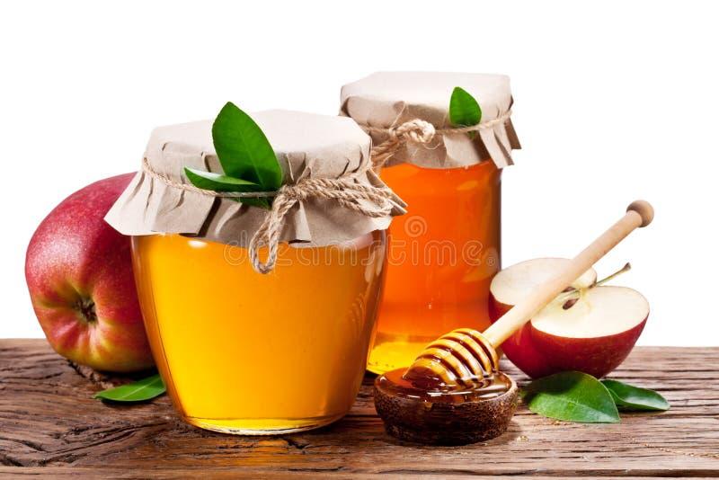 Σύνολο δοχείων γυαλιού του μελιού και των μήλων στο ξύλο στοκ εικόνα