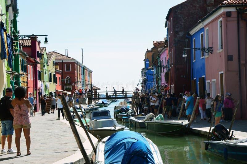 Σύνολο της Βενετίας Burano των τουριστών με τα χαρακτηριστικές ζωηρόχρωμες σπίτια, τις βάρκες και τη γέφυρά του στο κατώτατο σημε στοκ εικόνες με δικαίωμα ελεύθερης χρήσης