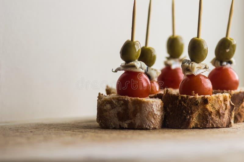 Σύνολο Pintxo Pintxos, ελιά, αντσούγια, ντομάτα κερασιών και ψωμί σε έναν αγροτικό πίνακα, τρόφιμα από τη βασκική χώρα στοκ εικόνες