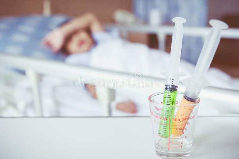 Σύριγγες σε ένα γυαλί που μετρά το φλυτζάνι με θολωμένο να βρεθεί αγοριών ασθένειας στοκ φωτογραφία με δικαίωμα ελεύθερης χρήσης