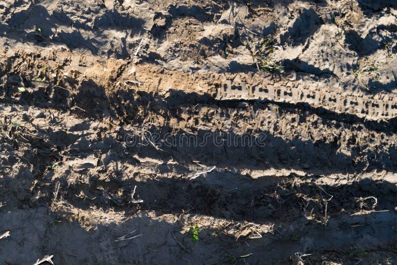Σύσταση ενός βρώμικου κακού βρώμικου δρόμου βρώμικων δρόμων με την ξήρανση της λάσπης με τις ρωγμές και τις αυλακιές Πλαϊνός στοκ εικόνα