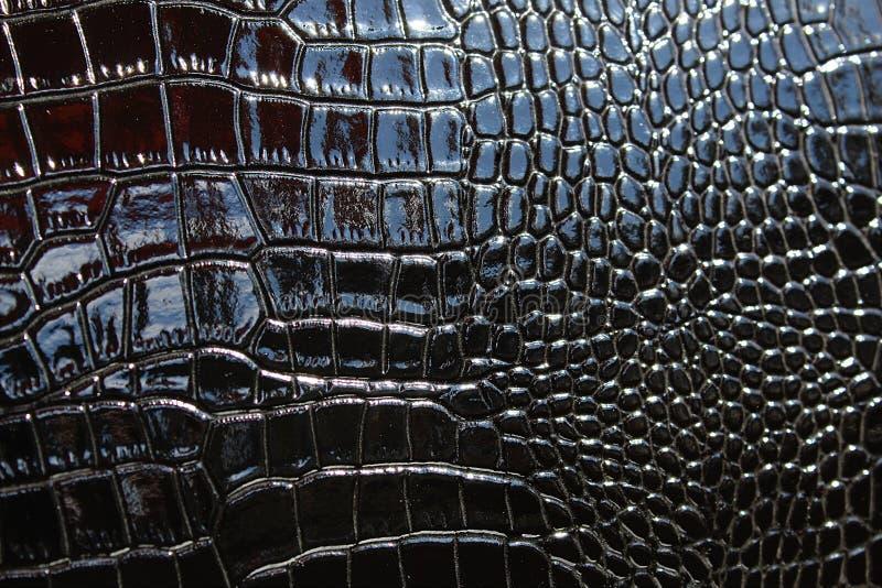 Σύσταση ενός λαμπρού μίμησης δέρματος κάτω από ένα μαύρο φίδι στοκ εικόνες