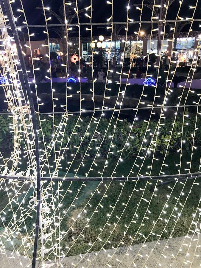 Σύσταση ενός πλήθους φωτεινών, λαμπρών όμορφων καμμένος εορταστικών νέων γιρλαντών Χριστουγέννων έτους ` s με τα φανάρια, μικροί  στοκ φωτογραφία με δικαίωμα ελεύθερης χρήσης