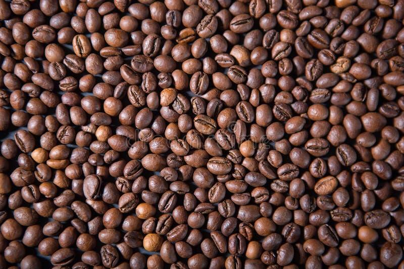Σύσταση και υπόβαθρο των ψημένων φασολιών καφέ που διασκορπίζονται στον πίνακα στοκ εικόνα