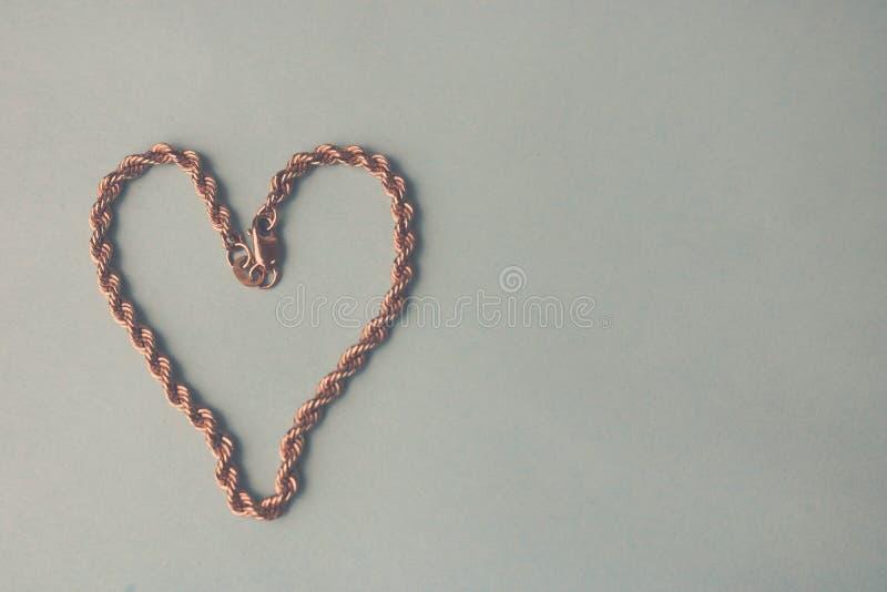 Σύσταση μιας όμορφης χρυσής εορταστικής μοναδικής ύφανσης αλυσίδων με μορφή μιας καρδιάς σε μια γραπτή θέση υποβάθρου και αντιγρά στοκ εικόνες