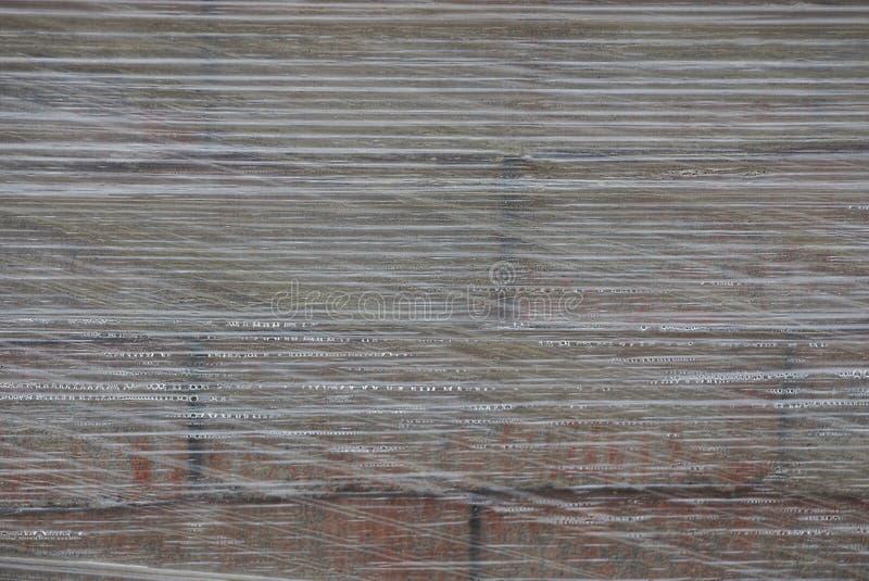 Σύσταση του διαφανούς γκρίζου σελοφάν στις πτώσεις νερού στα τούβλα στοκ φωτογραφία