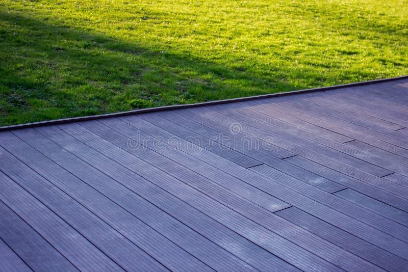 Σύσταση του ξύλινου υπαίθριου πατώματος με την πράσινη χλόη στοκ εικόνες