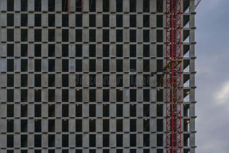Σύσταση του τεμαχίου ενός σύγχρονου σίδηρος-συγκεκριμένου τοίχου με τα παράθυρα χωρίς γυαλί Πρόσοψη των νέων multi-storey κτηρίων στοκ φωτογραφία με δικαίωμα ελεύθερης χρήσης
