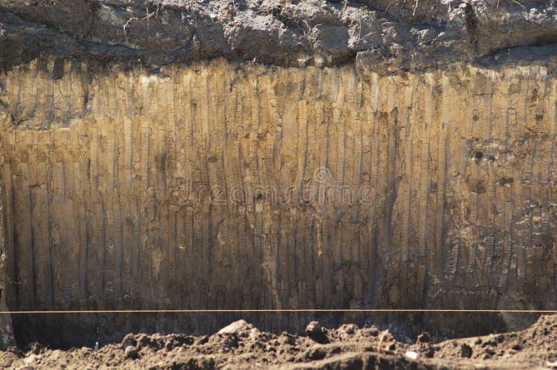 Σύσταση του χώματος με τα ίχνη ενός κάδου του εκσκαφέα Έδαφος τοίχων του κοιλώματος λατομείων τμημάτων για την οικοδόμηση κτηρίου στοκ φωτογραφία με δικαίωμα ελεύθερης χρήσης