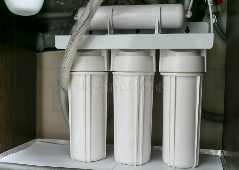 Σύστημα καθαρισμού νερού αντίστροφης όσμωσης στο σπίτι Εγκατάσταση των φίλτρων καθαρισμού νερού κάτω από το νεροχύτη κουζινών στο στοκ φωτογραφία με δικαίωμα ελεύθερης χρήσης