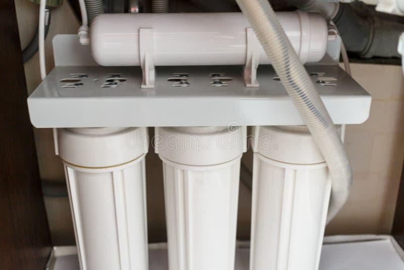 Σύστημα καθαρισμού νερού αντίστροφης όσμωσης στο σπίτι Εγκατάσταση των φίλτρων καθαρισμού νερού κάτω από το νεροχύτη κουζινών στο στοκ φωτογραφίες