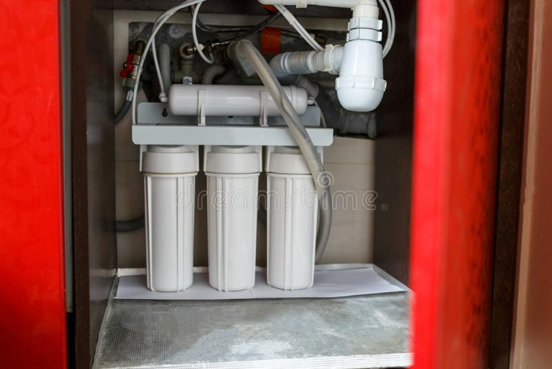 Σύστημα καθαρισμού νερού αντίστροφης όσμωσης στο σπίτι Εγκατάσταση των φίλτρων καθαρισμού νερού κάτω από το νεροχύτη κουζινών στο στοκ εικόνες