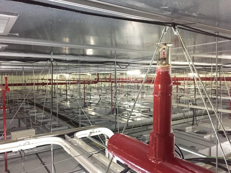 Σύστημα ψεκαστήρων πυρκαγιάς με τους κόκκινους σωλήνες στη μονάδα φίλ στοκ φωτογραφία με δικαίωμα ελεύθερης χρήσης