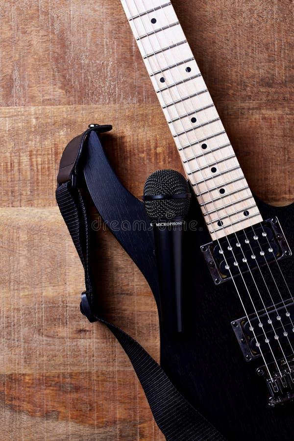 Σώμα και fretboard της σύγχρονων ηλεκτρικών κιθάρας και του μικροφώνου στο αγροτικό ξύλινο υπόβαθρο στοκ εικόνα με δικαίωμα ελεύθερης χρήσης