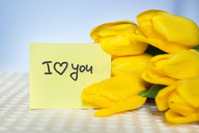 Σ' αγαπώ, κάρτα με τις λέξεις και τα κίτρινα λουλούδια τουλιπών στοκ φωτογραφία με δικαίωμα ελεύθερης χρήσης