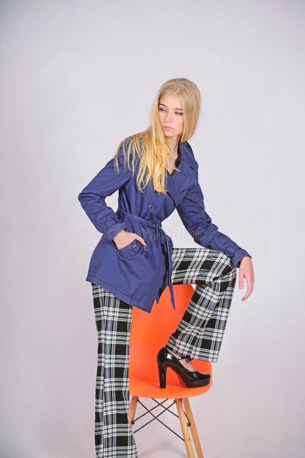 Τάση μόδας παλτών τάφρων Πρέπει να έχετε την έννοια Πρόσωπο γυναικών makeup που θέτει το παλτό στη σύγχρονη καρέκλα Μοντέρνο παλτ στοκ φωτογραφία με δικαίωμα ελεύθερης χρήσης