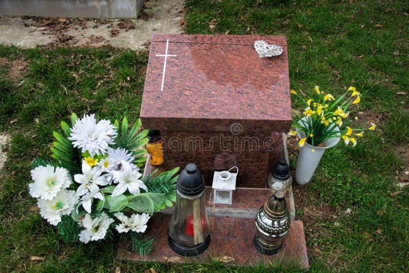 Τάφος δοχείων με το σταυρό στο παραδοσιακό νεκροταφείο Votive φανάρι και λουλούδια κεριών στις πέτρες τάφων στο νεκροταφείο Όλο τ στοκ εικόνα
