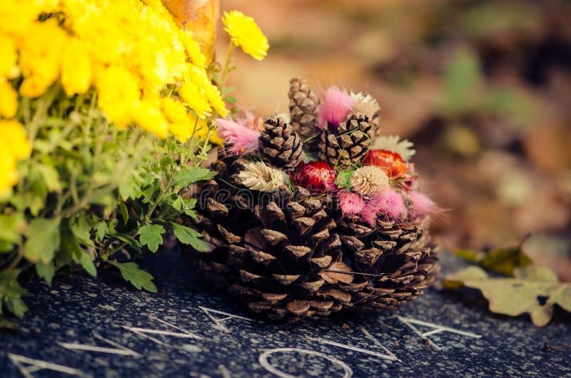Τάφος που καλύπτεται από τα φθινοπωρινούς φύλλα και τον κώνο πεύκων στοκ φωτογραφίες