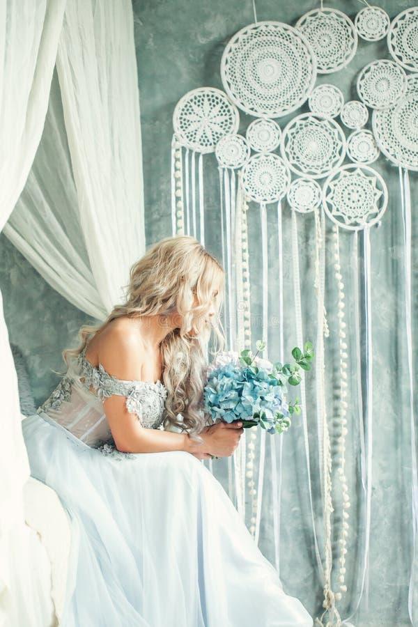 Τέλεια γυναίκα ομορφιάς με την ξανθή σγουρή τρίχα και λουλούδια στο εκλεκτής ποιότητας εσωτερικό στοκ εικόνες