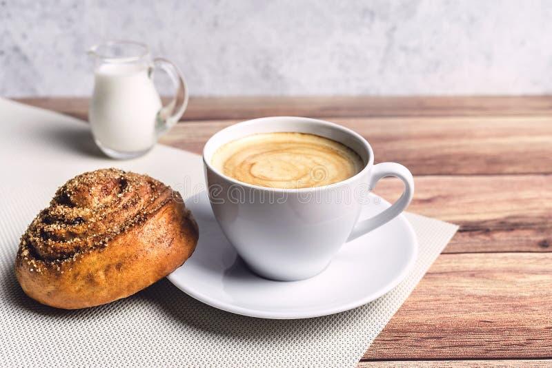 Τέλειο πρόγευμα ενός σπιτικών κουλουριού κανέλας, ενός καφέ και μιας κανάτας γάλακτος γυαλιού στον ξύλινο πίνακα r στοκ φωτογραφία