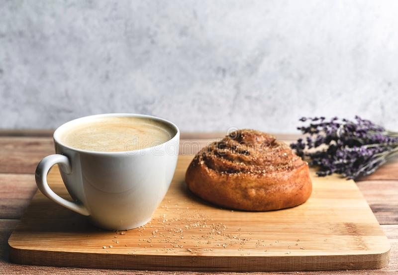 Τέλειο πρόγευμα του σπιτικών κουλουριού και του καφέ κανέλας στον ξύλινο πίνακα που διακοσμείται με lavender r στοκ εικόνα με δικαίωμα ελεύθερης χρήσης
