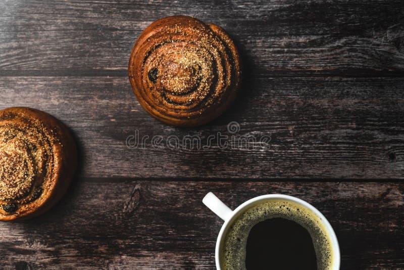 Τέλειο πρόγευμα των σπιτικών κουλουριών και του καφέ κανέλας στον ξύλινο πίνακα Αγροτικό ύφος στοκ εικόνα