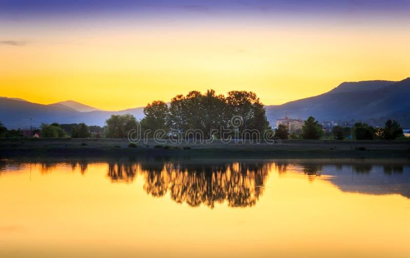 Τέλειο χρυσό ηλιοβασίλεμα ώρας πέρα από την ήρεμη, αντανακλαστική λίμνη στοκ εικόνα