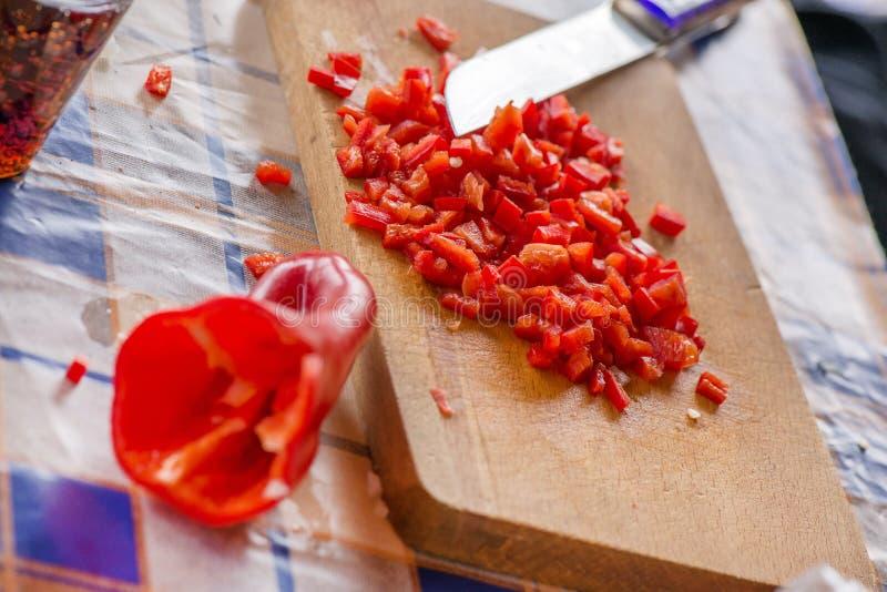 Τέμνοντα γλυκά κόκκινα πάπρικα και κρεμμύδια στον ξύλινο τέμνοντα πίνακα στοκ εικόνα με δικαίωμα ελεύθερης χρήσης