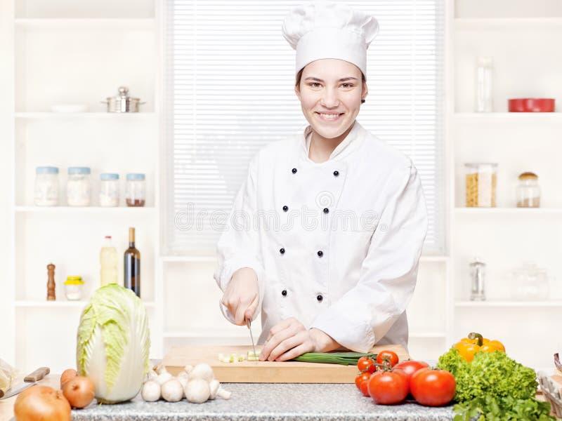 τέμνοντα θηλυκά κρεμμύδια κουζινών αρχιμαγείρων στοκ φωτογραφίες