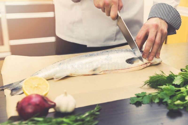 Τέμνοντα ψάρια σολομών αρχιμαγείρων στην κουζίνα εστιατορίων στοκ εικόνα με δικαίωμα ελεύθερης χρήσης