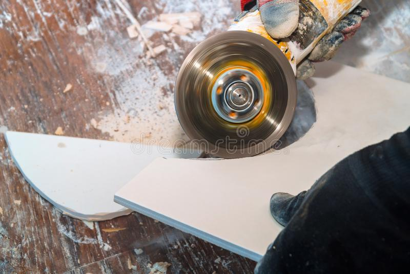 Τέμνον κεραμίδι εργαζομένων που χρησιμοποιεί το μύλο που κόβεται στα στρώματα των κεραμικών κεραμιδιών πατωμάτων στοκ φωτογραφία