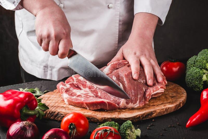 Τέμνον κρέας χοιρινού κρέατος χασάπηδων αρχιμαγείρων με το μαχαίρι στην κουζίνα, μαγειρεύοντας τρόφιμα στοκ φωτογραφίες με δικαίωμα ελεύθερης χρήσης