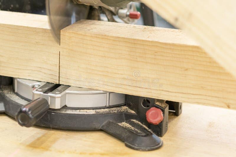 τέμνον ξύλινο χρησιμοποιώντας επιτραπέζιο πριόνι ξυλουργών ατόμων στο εργοτάξιο οικοδομής στοκ εικόνα