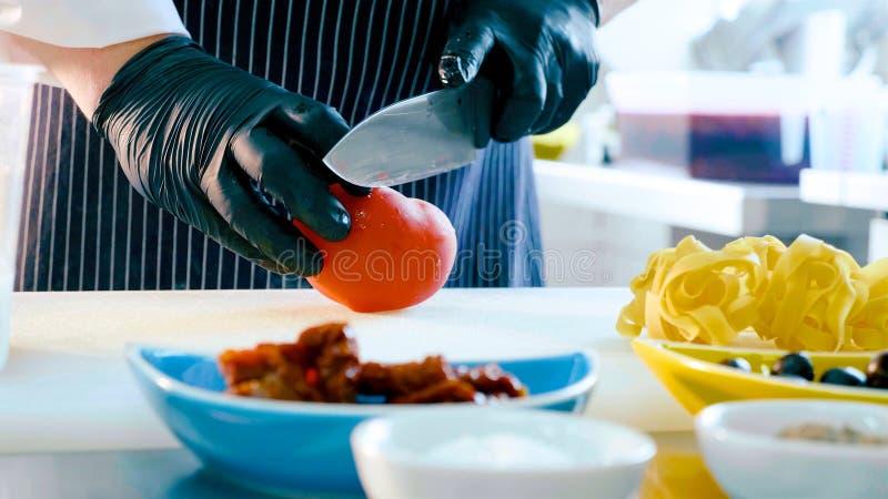 Τέμνουσα ντομάτα αρχιμαγείρων για την προετοιμασία των ιταλικών τροφίμων στοκ εικόνες με δικαίωμα ελεύθερης χρήσης
