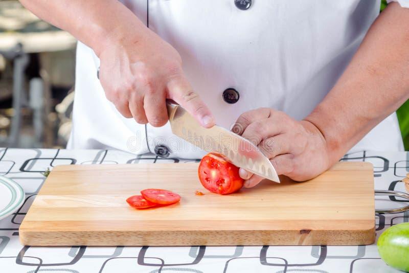 Τέμνουσα ντομάτα αρχιμαγείρων στοκ φωτογραφίες