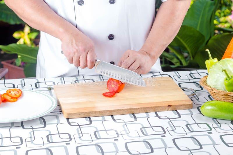Τέμνουσα ντομάτα αρχιμαγείρων στοκ εικόνες