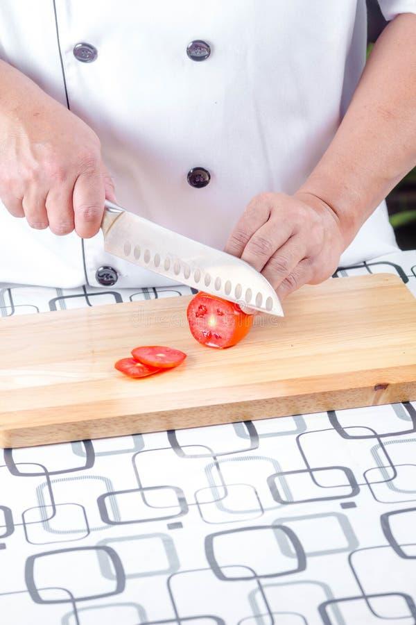 Τέμνουσα ντομάτα αρχιμαγείρων στοκ φωτογραφίες με δικαίωμα ελεύθερης χρήσης