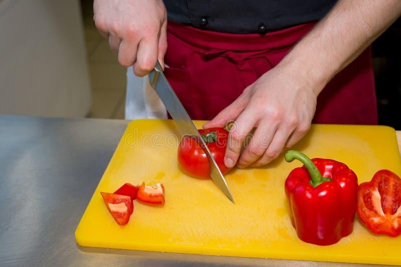 Τέμνουσα πάπρικα σκληρών ανδρών στην κουζίνα Χέρια αρχιμάγειρα με το μαχαίρι που κόβει την κόκκινη πάπρικα στον τέμνοντα πίνακα γ στοκ εικόνα με δικαίωμα ελεύθερης χρήσης