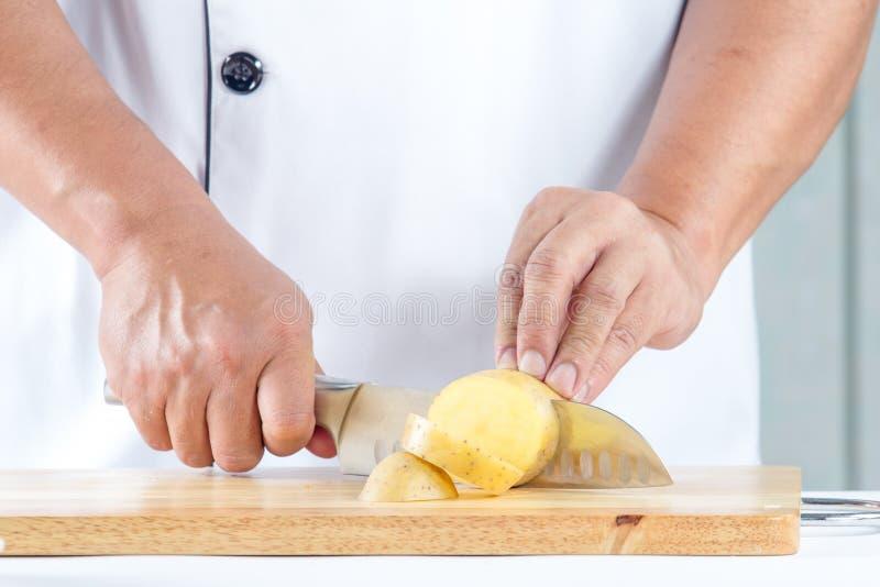 Τέμνουσα πατάτα αρχιμαγείρων στοκ εικόνα