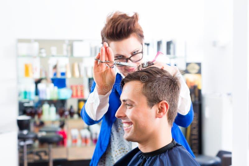 Τέμνουσα τρίχα ατόμων κομμωτών στο barbershop στοκ εικόνες