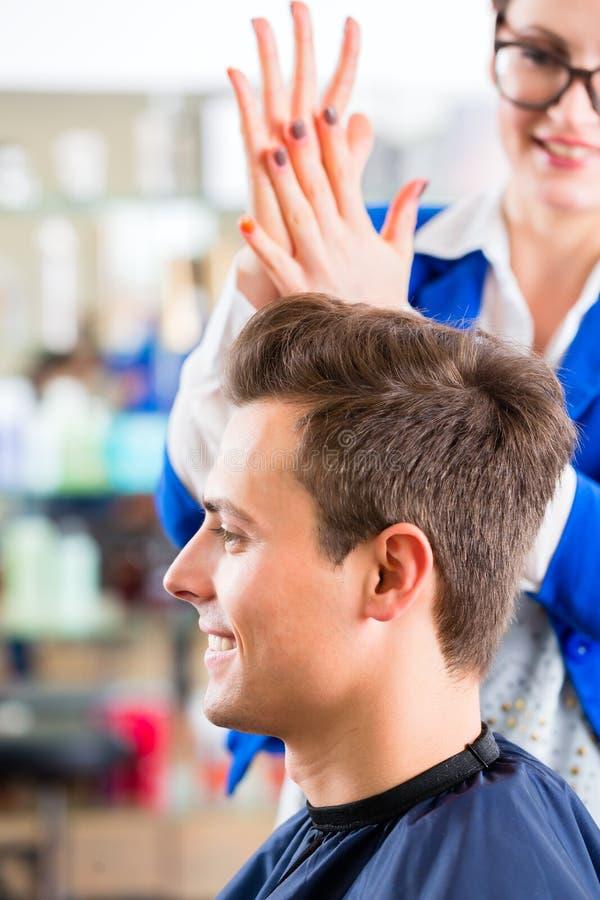 Τέμνουσα τρίχα ατόμων κομμωτών στο barbershop στοκ εικόνα με δικαίωμα ελεύθερης χρήσης