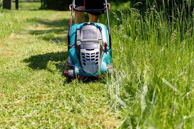 Τέμνουσα χλόη ατόμων με έναν ηλεκτρο χορτοκόπτη στον κήπο του στοκ φωτογραφία με δικαίωμα ελεύθερης χρήσης
