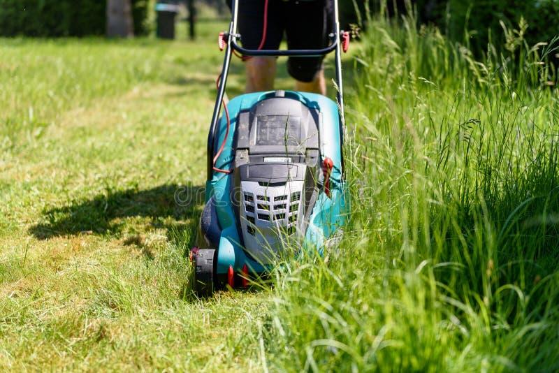 Τέμνουσα χλόη ατόμων με έναν ηλεκτρο χορτοκόπτη στον κήπο του στοκ φωτογραφίες