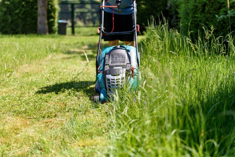 Τέμνουσα χλόη ατόμων με έναν ηλεκτρο χορτοκόπτη στον κήπο του στοκ εικόνες