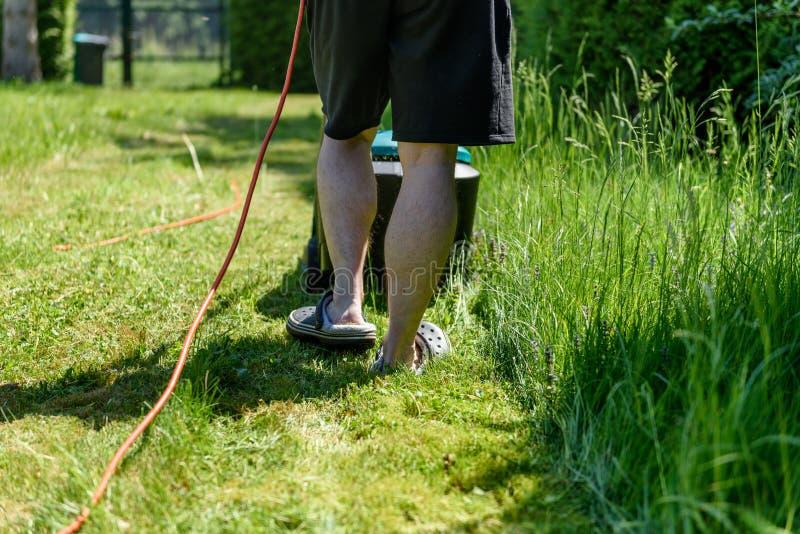 Τέμνουσα χλόη ατόμων με έναν ηλεκτρο χορτοκόπτη στον κήπο του στοκ εικόνα με δικαίωμα ελεύθερης χρήσης