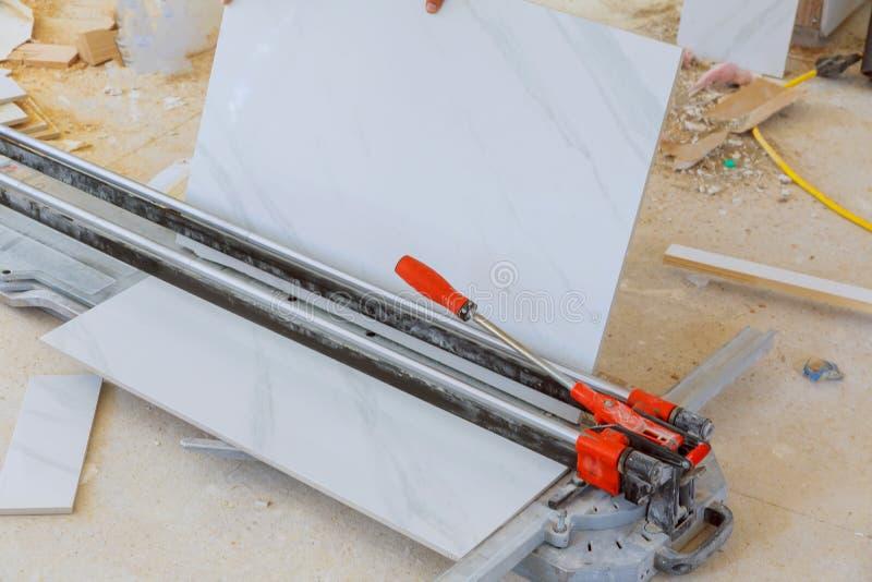 Τέμνων εργαζόμενος που εργάζεται με το κεραμίδι πατωμάτων που κόβει το βιομηχανικό εξοπλισμό στην εργασία ανακαίνισης επισκευής στοκ εικόνες