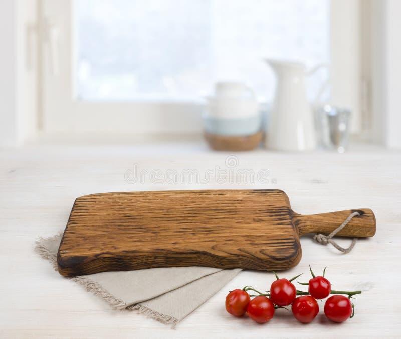 Τέμνων πίνακας επάνω από το τραπεζομάντιλο λινού στον ξύλινο πίνακα Έννοια μαγειρέματος στοκ εικόνες